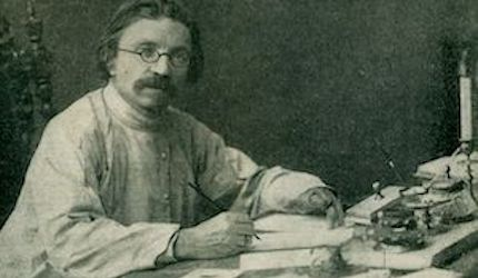 Middle aged man with round eye glasses sitting at a writing desk